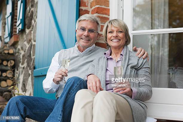 Germany, Kratzeburg, Senior couple sitting on terrace of country house with champagne flute