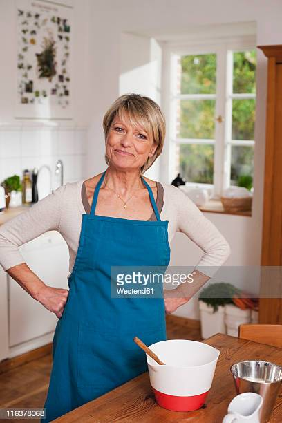 germany, kratzeburg, senior woman preparing food, portrait - main sur la hanche photos et images de collection