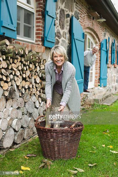 Germany, Kratzeburg, Senior woman with firewood, senior man in background