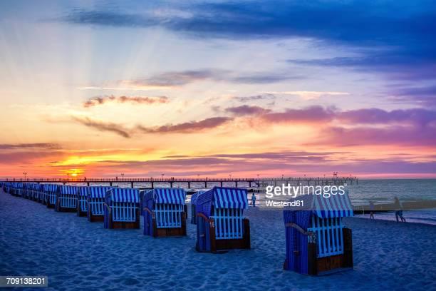 Germany, Kuehlungsborn, sea bridge and beach chairs at sunrise