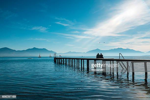 Germany, Lake Chiemsee, Seebruck, two people on wooden jetty