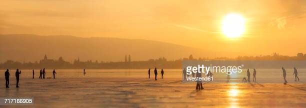 germany, lake constance hegne, silhouettes of ice skaters and walkers in front of reichenau at sunset - baden württemberg stock-fotos und bilder