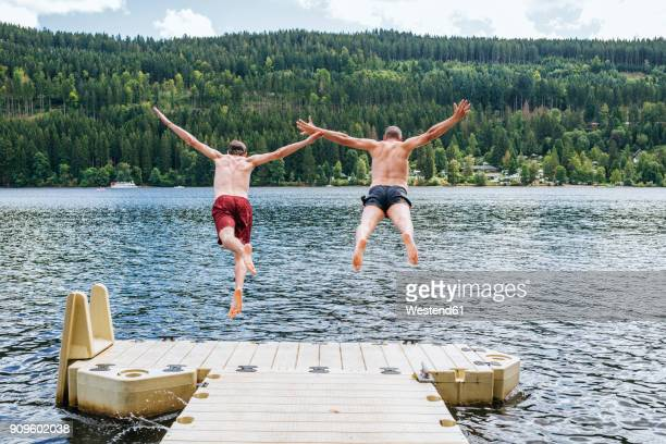 Germany, Lake Titisee, two men jumping into lake from a jetty