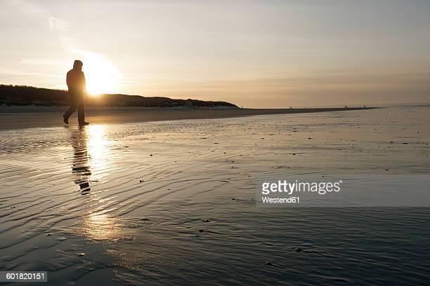 Germany, Langeoog Island, man walking on the beach at sunset