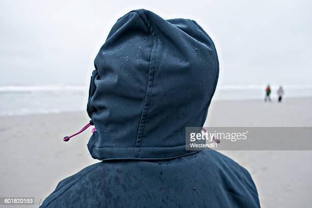germany, langeoog island, person with wet hood on the beach - insel langeoog stock-fotos und bilder