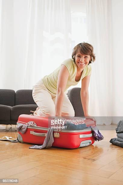 Germany, Leipuig, Woman kneeling on suitcase, smiling, portrait