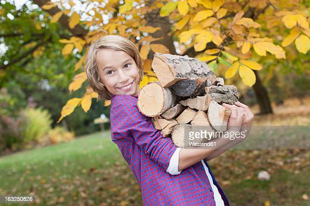 germany, leipzig, boy holding firewood, smiling - firewood stock pictures, royalty-free photos & images