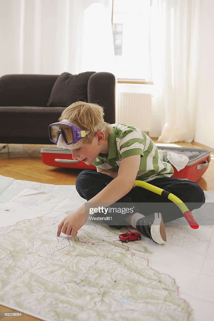 Germany, Leipzig, Boy (8-9) sitting on map wearing diving goggles, smiling, portrait : Stock Photo