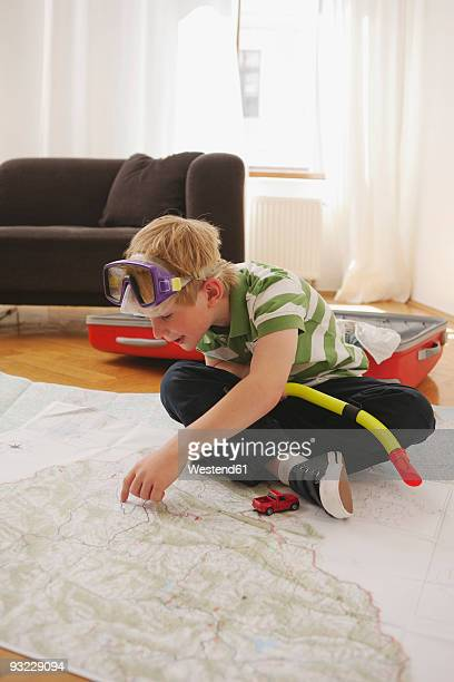 Germany, Leipzig, Boy (8-9) sitting on map wearing diving goggles, smiling, portrait