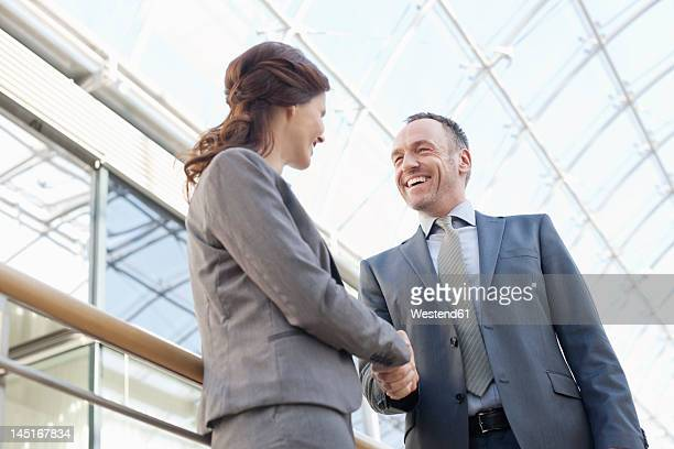 Germany, Leipzig, Business people shaking hands, smiling