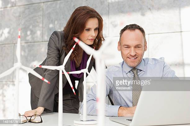 Germany, Leipzig, Business people using laptop and discussing about wind power model