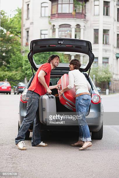 Germany, Leipzig, Couple loading luggage into car, smiling