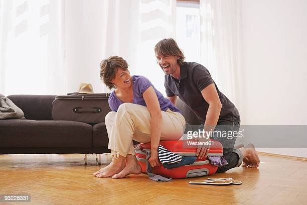 Germany, Leipzig, Couple packing a suitcase, laughing