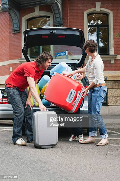 Germany, Leipzig, Parents with son (8-9) loading luggage into car