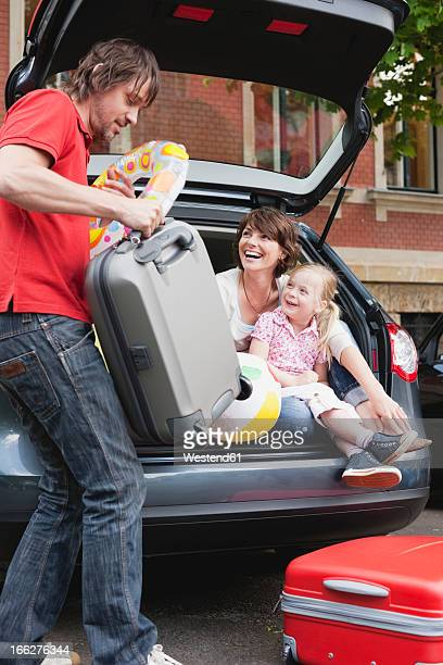 Germany, Leipzig, Family with young girl (8-9) loading luggage into car
