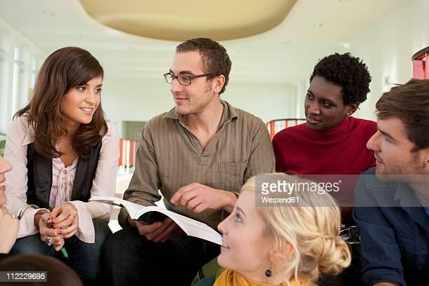Germany, Leipzig, Group of university students sitting together, smiling