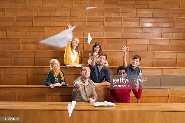 Germany, Leipzig, Group of university students throwing papers aeroplane and enjoying in classroom