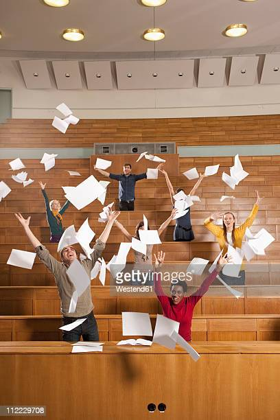 Germany, Leipzig, Group of university students throwing papers in classroom