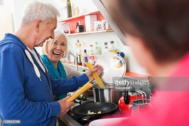Germany, Leipzig, Man and women cooking food, smiling