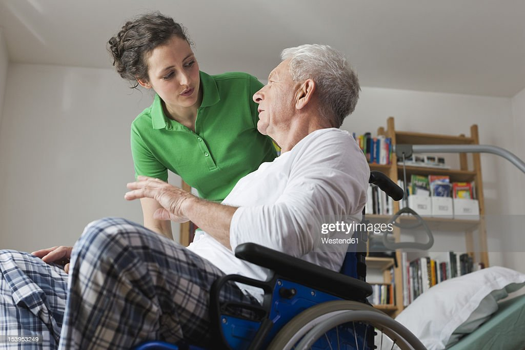 Germany, Leipzig, Man on wheelchair, talking with woman : Stock Photo