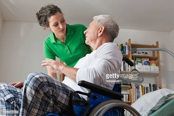 germany, leipzig, man on wheelchair, talking with woman - outpatient care stock pictures, royalty-free photos & images