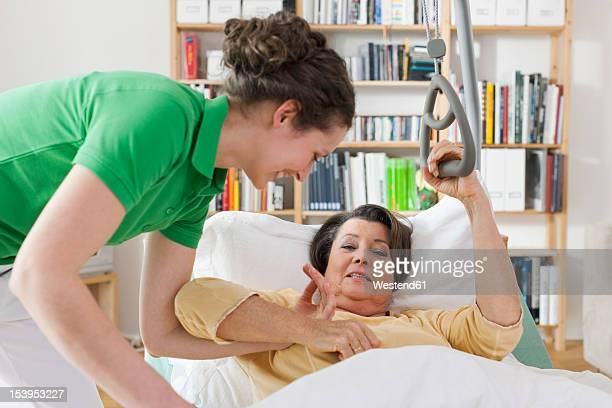 Germany, Leipzig, Mid adult woman helping senior woman