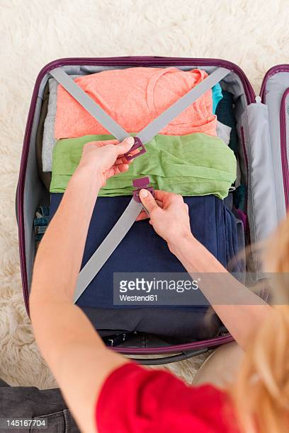 Germany, Leipzig, Mid adult woman packing suitcase for vacation