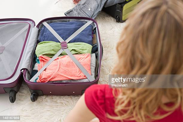 Germany, Leipzig, Mid adult woman packing suitcase