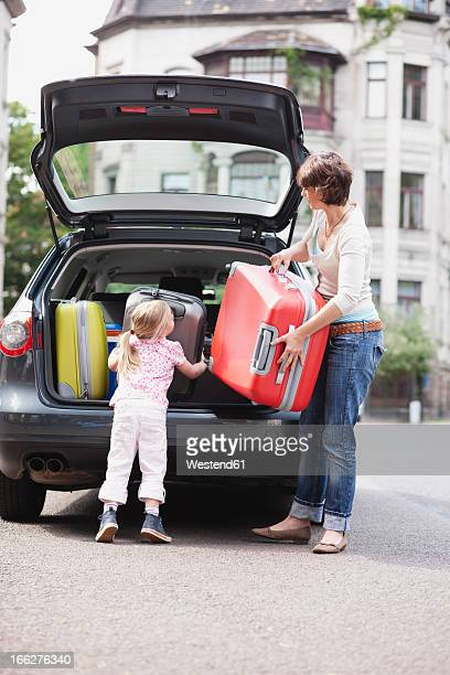 Germany, Leipzig, Mother and daughter (4-5) loading luggage into car