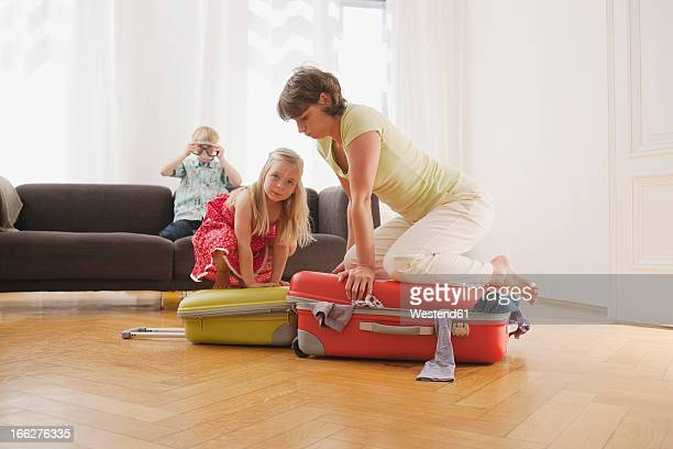 Germany, Leipzig, Mother and daughter (4-5) struggling to pack suitcase with boy (8-9) watching from sofa