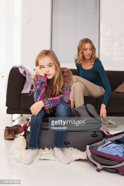 Germany, Leipzig, Mother and daugther with packed luggage in apartment