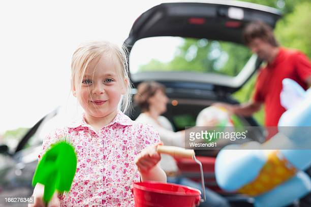 Germany, Leipzig, Girl (4-5) holding plastic spade and bucket with parents loading car in background