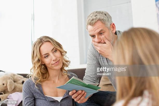 germany, leipzig, parents watching school report of girl - boletim escolar imagens e fotografias de stock