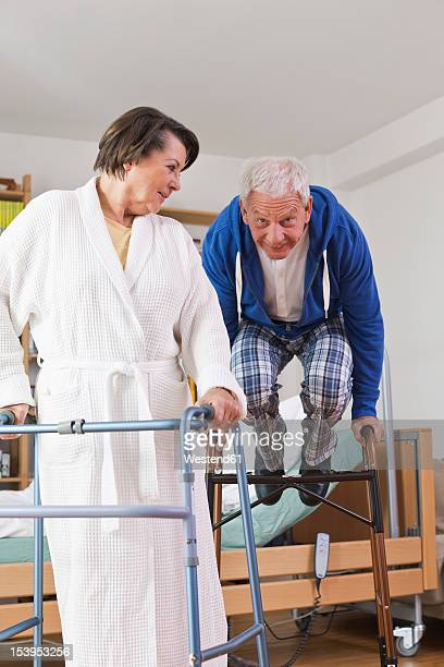 Germany, Leipzig, Senior man and woman with walking frame while man jumping