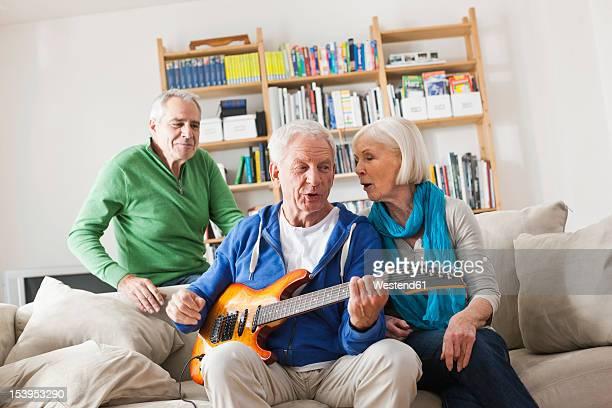 Germany, Leipzig, Senior man playing electric guitar, man and woman sitting besides