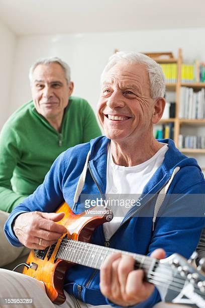 Germany, Leipzig, Senior man playing electric guitar, man sitting in background