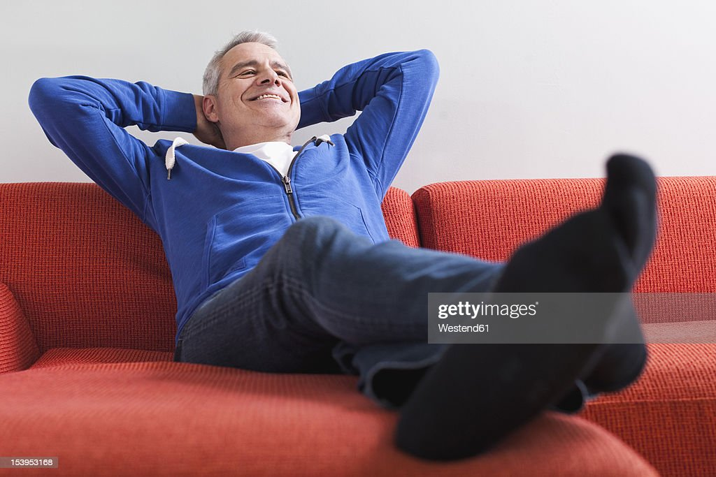 Germany, Leipzig, Senior man relaxing on couch, smiling : Stock Photo