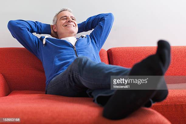 germany, leipzig, senior man relaxing on couch, smiling - legs crossed at ankle stock pictures, royalty-free photos & images