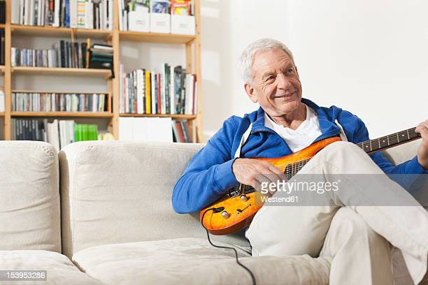 germany, leipzig, senior man sitting on sofa and plucking guitar - 60 64 years stock pictures, royalty-free photos & images