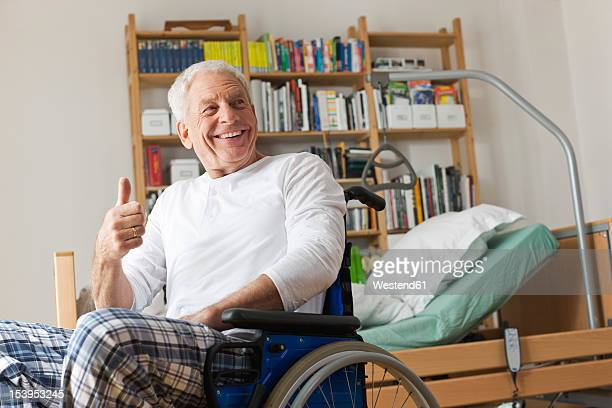 Germany, Leipzig, Senior man sitting on wheelchair, showing thumbs up