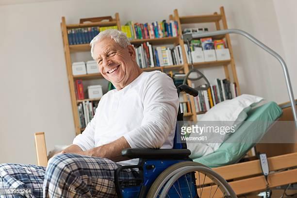 Germany, Leipzig, Senior man sitting on wheelchair, smiling