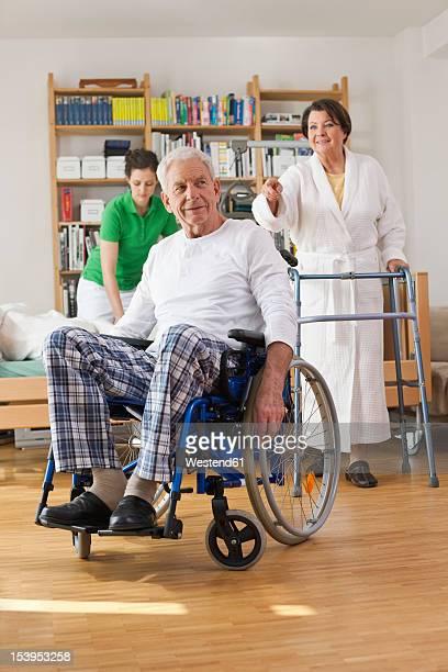 Germany, Leipzig, Senior man sitting on wheelchair, woman with walking frame