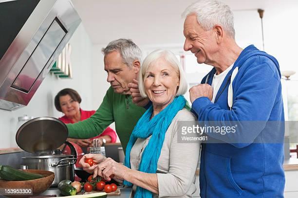 Germany, Leipzig, Senior men and women cooking food