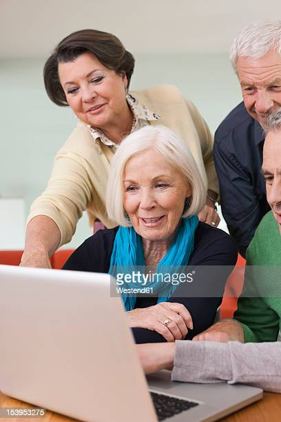 Germany, Leipzig, Senior men and women watching pictures on laptop