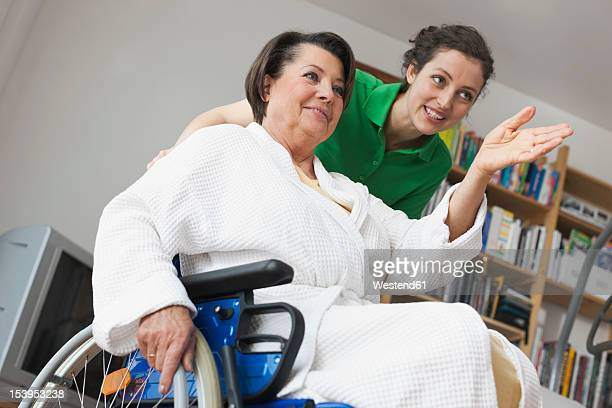 Germany, Leipzig, Senior woman sitting on wheelchair while another woman pushing