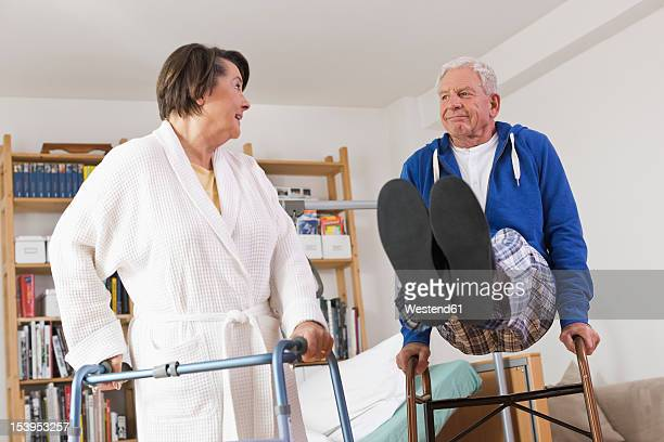 Germany, Leipzig, Senior woman standing and man playing with walking frame