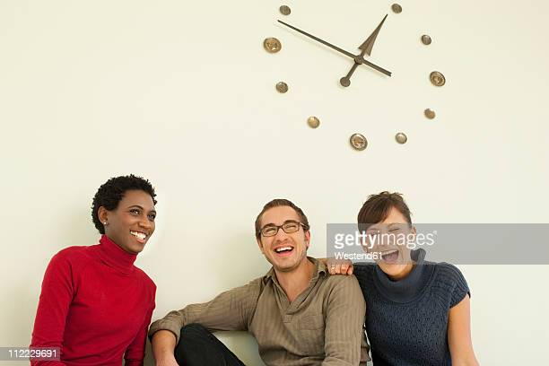 germany, leipzig, university students sitting against wall clock, smiling - ver a hora imagens e fotografias de stock