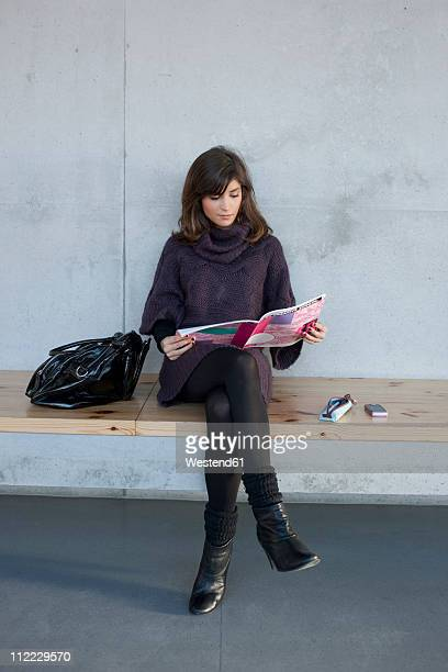 Germany, Leipzig, Woman sitting and reading magazine