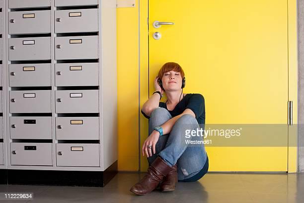 germany, leipzig, young woman sitting and listening music in locker room - leipzig saksen stockfoto's en -beelden