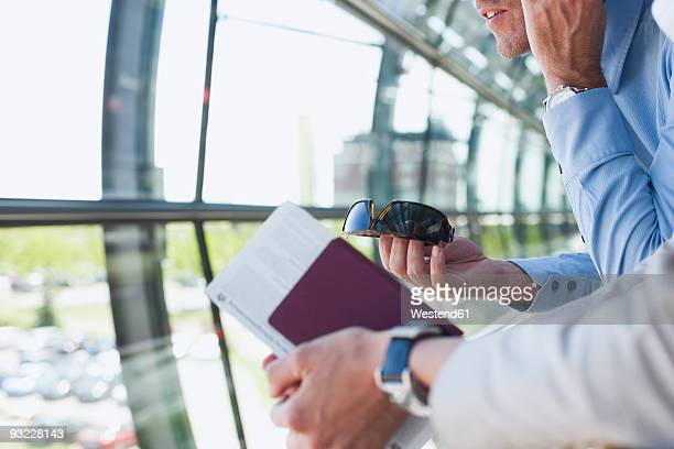 Germany, Leipzig-Halle, Airport, Businessman using mobile phone, businesswoman in foreground